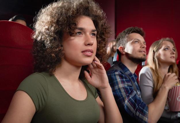 Вид со стороны возбужденной девушки, смотрящей интригующий фильм.