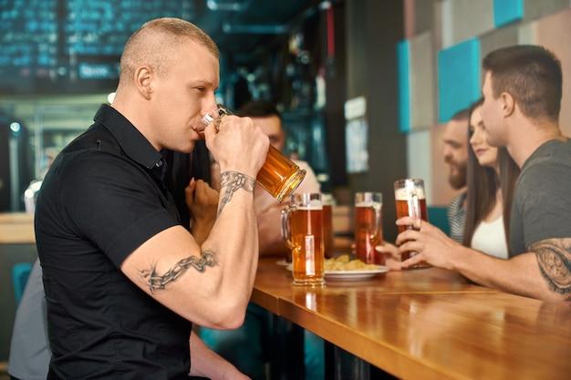 테이블에 앉아 술집에서 맥주를 마시는 강한 문신을 한 남자의 측면에서 볼 수 있습니다. 맥주와 함께 파인트를 유지하고 친구와 함께 저녁을 즐기는 검은 셔츠에 젊은 운동 남성. 음료의 개념.