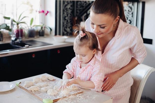 女性とかわいい娘が一緒に料理する側からの眺め