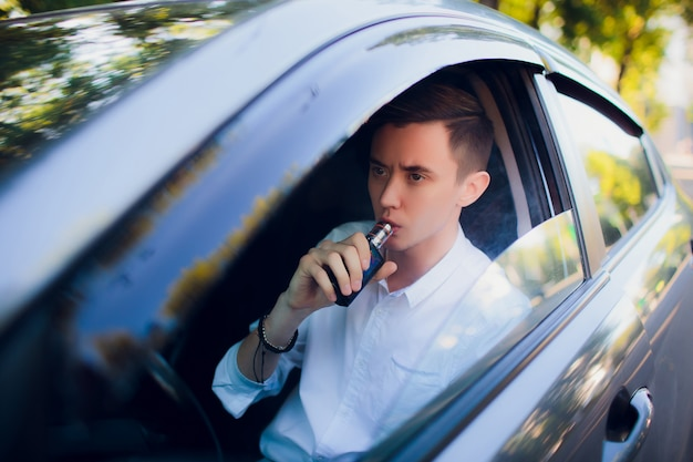 View from side young man smoking an e-cigarette as he drives his car on an urban street. car driver peeps out of the car and smokes