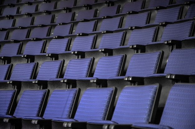 View from stairs on rows of comfortable blue chairs in theater or cinema . curve of blue seats