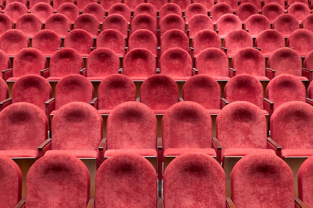 View from stairs on rows of comfortable red chairs in theater