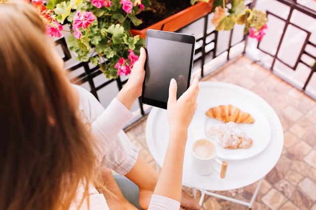 View from above tablet in hands of girl in pajama sitting surround flowers on balcony, having breakfast in the morning.