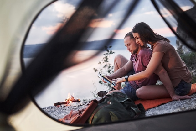 View from tent of couple with map lying a view of lake during hiking trip.