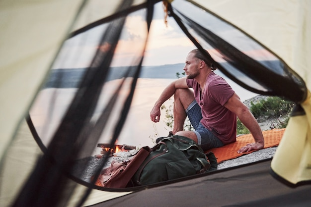 View from tent of traveller with backpack sitting on top of mountain enjoying view coast a river or lake.