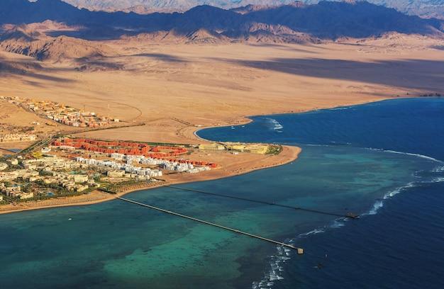 Вид из окна самолета на горы и морской курорт египта шарм-эль-шейх