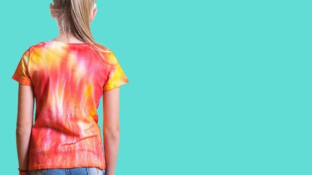 Вид сзади девушки в футболке в стиле тай-дай на бирюзовом фоне. белая одежда раскрашена вручную.