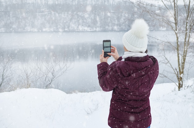 スマートフォンを持って美しい雪を撮影している暖かい服を着た女性の後ろからの眺め