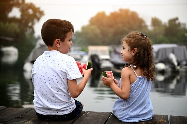 幼稚園児と男子生徒の2人の子供の後ろからの眺め、スイカを食べてお互いを見つめ、暖かい夏の夜に桟橋に座って美しい夕日を楽しんでいます