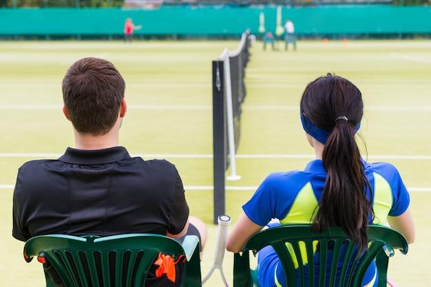 テニスコートの椅子で休んでいるスポーツウェアを着ているテニスプレーヤーのカップルの後ろからの眺め