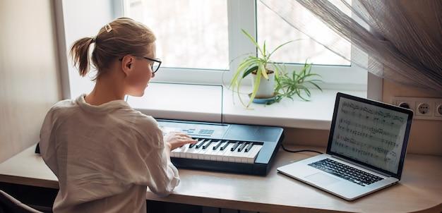 Вид сзади молодая женщина играет на синтезаторе, читает заметки на экране ноутбука. самостоятельное обучение игре на фортепиано в домашних условиях. увлечение музыкой, хобби, отдых, саморазвитие.