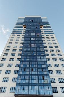 Вид снизу многоэтажного жилого дома на фоне ясного неба