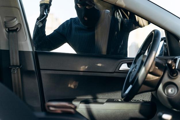 검은 옷을 입은 남자가 머리에 발라클라바를 하고 도둑질하기 전에 지렛대로 차 유리를 깨려고 준비하는 남자의 차에서 봅니다. 자동차 도둑, 자동차 절도 개념