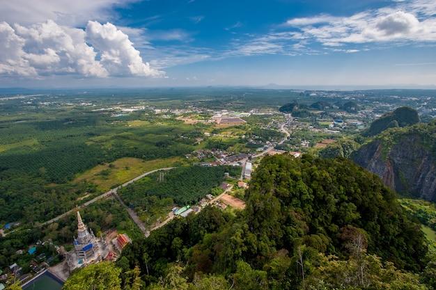 Вид со скалы на храм тигровой пещеры и зеленые поля. небольшие домики вдалеке. облака в голубом небе.