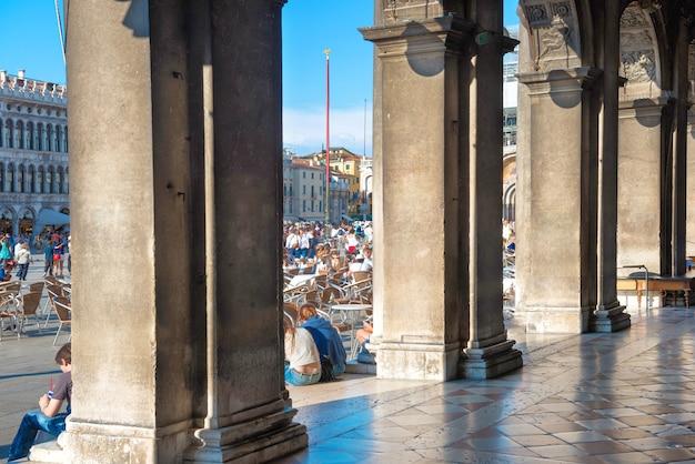 이탈리아 베니스의 산 마르코 광장에 있는 관광객들, 도제 궁전의 기둥에서 보기