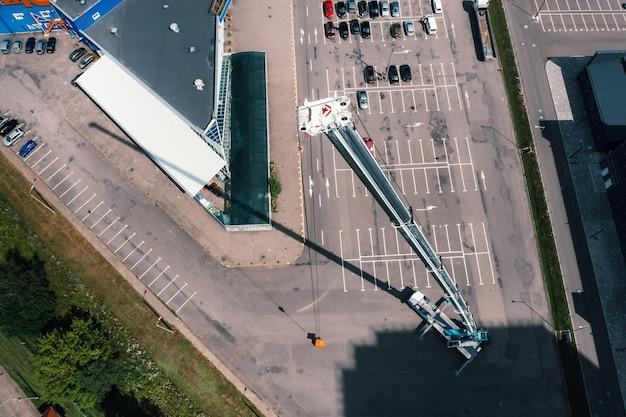Вид с высоты на автомобиль-тяжелый кран, стоящий на стоянке в открытом виде и готовый к работе. на площадке развернут самый высокий автокран. высота стрелы 80 метров.