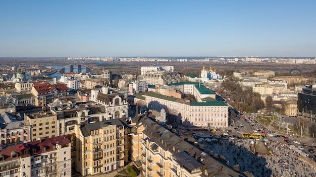 Вид с высоты на город киев и его районы. современные здания в центре города, андреевская церковь, подольский мост и левый берег города киев, украина. фото дрона