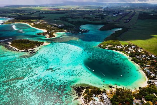 모리셔스 섬의 동쪽 해안 높이에서 볼 수 있습니다. belle mare 지역의 모리셔스 섬에서 가장 아름다운 해변과 청록색 석호 위로 비행
