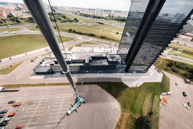 도시의 유리 건물 근처 주차장에 열려 있고 작업 할 준비가 된 가장 높은 자동차 크레인의 높이에서 볼 수 있습니다.
