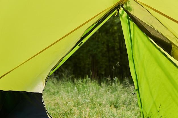 개방된 입구를 통해 여름에 하이킹 돔 텐트에서 숲으로의 전망