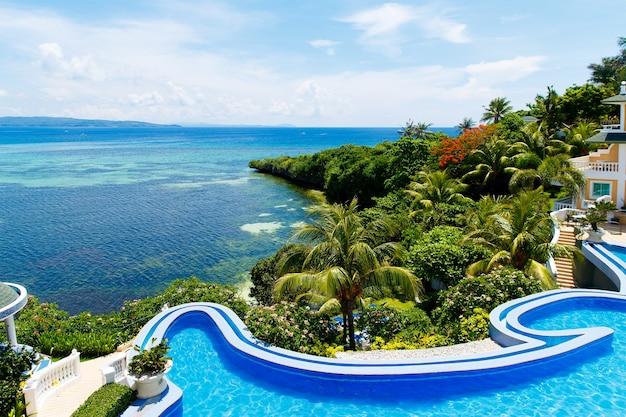 トロピカルビーチのインフィニティプールとボートのある美しい海のあるホテルからの眺め