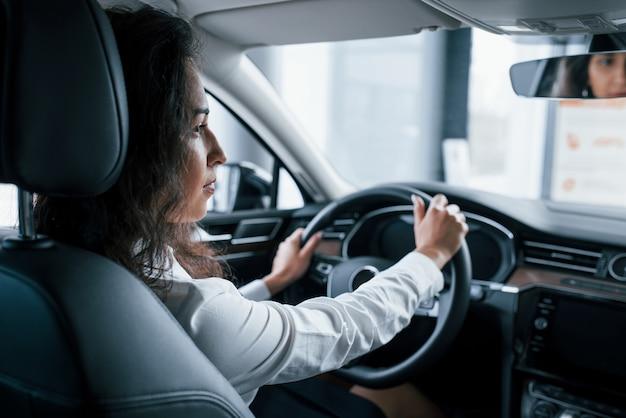 内側からの眺め。自動車サロンで彼女の新しい車をしようとしている美しい女性実業家