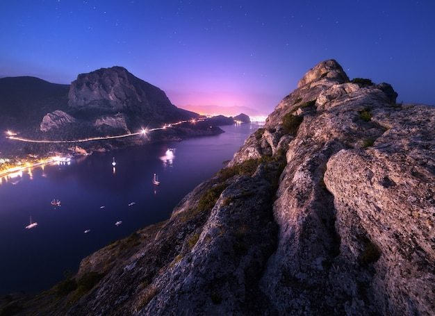 夜の街の山頂、青い海、美しい空を背景にした高い岩からの眺め。夜のカラフルな山の風景。海岸での休暇。ヨーロッパの夏の旅行。街の明かり