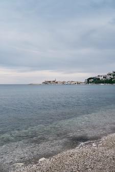 자갈 해변에서 바다 산과 건물의 전망