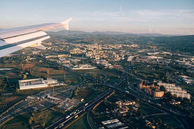 高層ビルが高速道路と緑を輸送する近代的な都市の飛行機の窓からの眺め