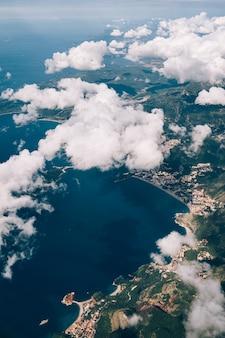 白い積雲を通してモンテネグロの海岸の飛行機の窓からの眺め
