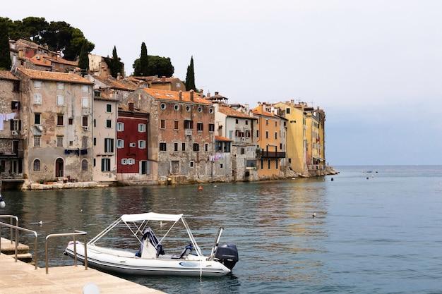 Вид с моря на побережье старого города ровинь с разноцветными домами на закате, хорватия