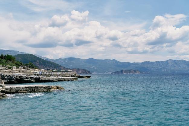 일광욕용 긴 의자와 초가 우산이 있는 바다에서 바위 해안까지의 전망