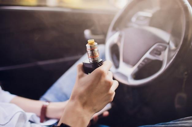 Вид со стороны молодого человека, курящего электронную сигарету, когда он ведет свой автомобиль на городской улице. удерживает и регулирует мощность электронной сигареты.