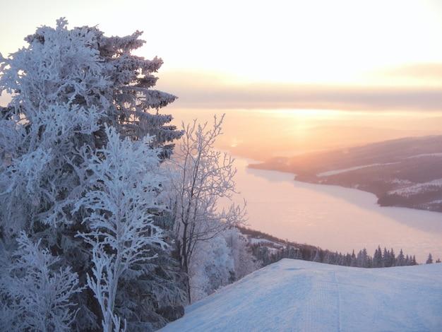 夜明けの凍った川のスキー場からの眺め。