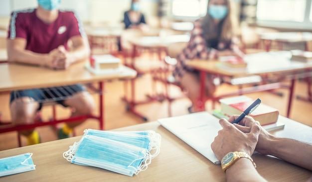 코로나바이러스 질병에 대한 보호 마스크를 착용한 학생들의 교사 책상에서 봅니다.