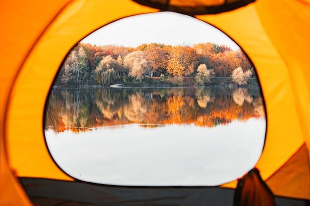 Вид из палатки на озеро с желтыми деревьями лес на другой стороне пляжа