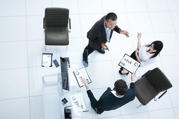 上からの眺め。オフィスに立っている財務書類について話し合うビジネスチーム