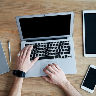 나무 테이블에서 노트북과 스마트폰으로 작업하는 맨 위 손에서 보기