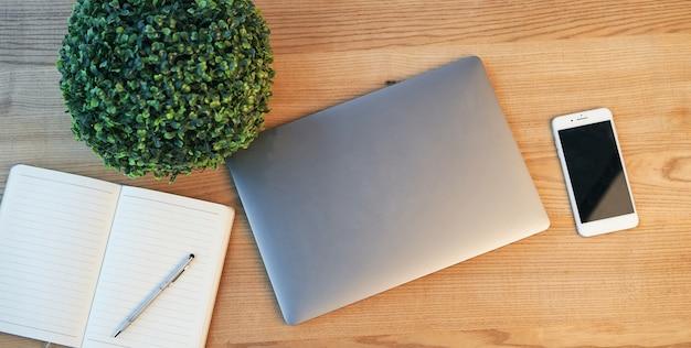 上からの眺め、ノートパソコンとスマートフォンの木製テーブル