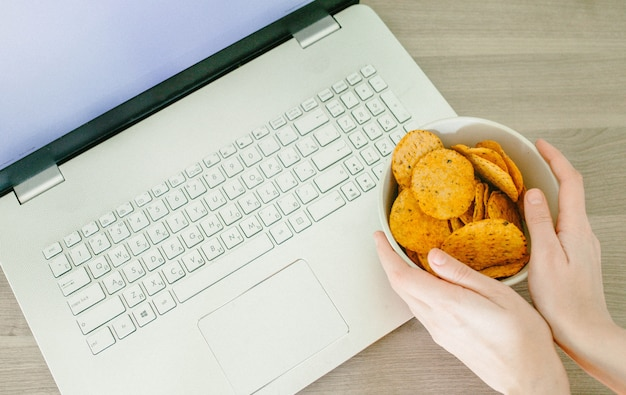 Вид сверху на ноутбук и женские руки с чипсами