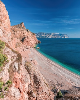 Вид с вершины скалы на пляж с лазурным морем, солнечным днем и чистым небом