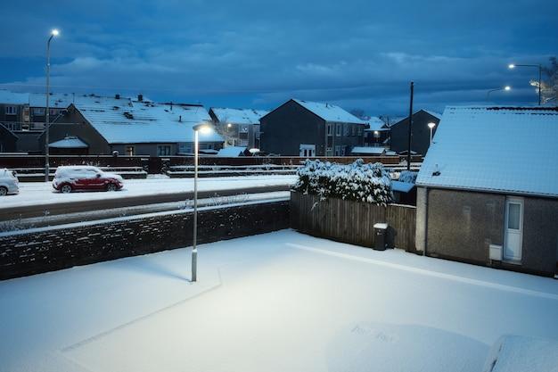 冬のアーマデールウェストロージアンのスコットランドの町の雪に覆われた夜の中庭の頂上からの眺め...
