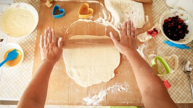Вид сверху на молодую женщину, делающую тесто и раскатывающую его деревянной скалкой на кухонной стойке