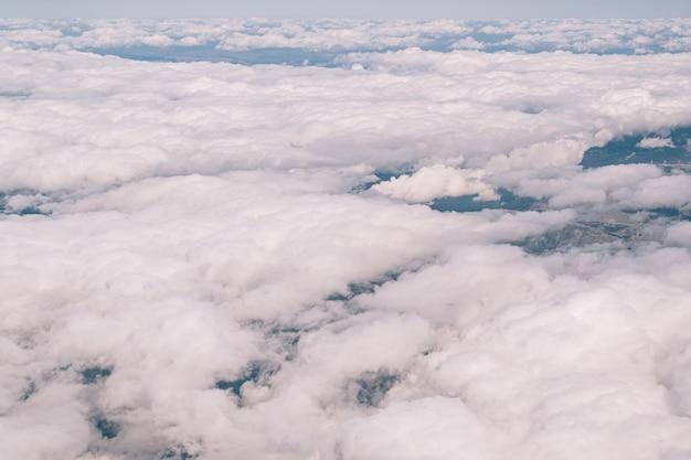 Вид из окна самолета на белые кучевые облака в небе