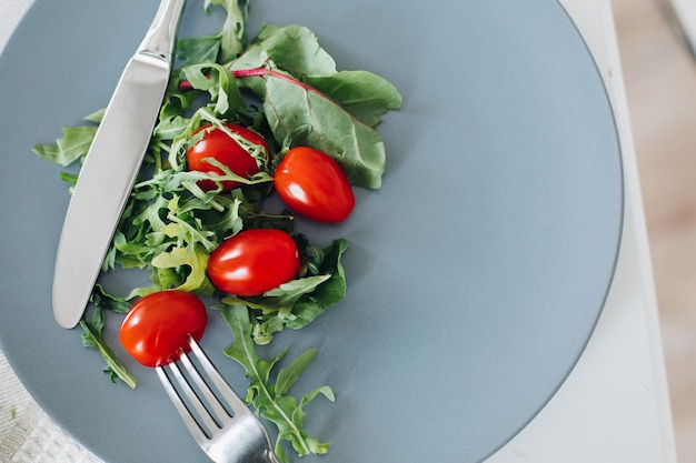 View from above of tomatoes and greens lying on plate