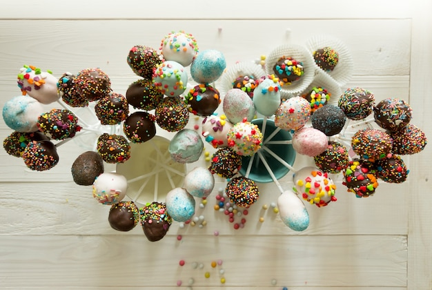 View from top on beautiful colorful cake pops on wooden table