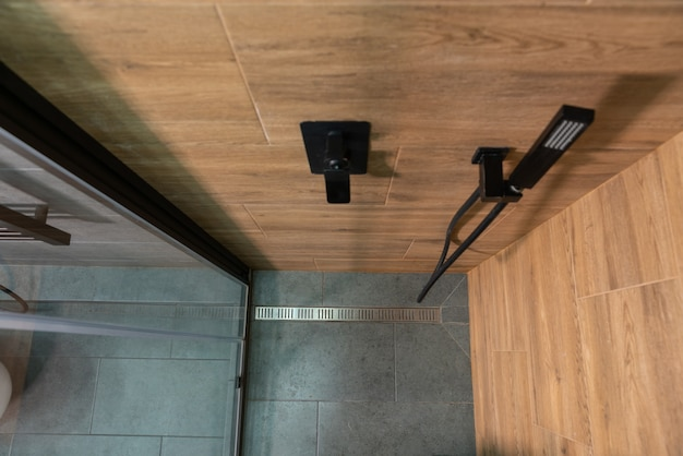 View from the top of the cubicle looking down into a shower with wood pattern tiled walls and grey tiled floor with metal drain past the mixer tap and shower head