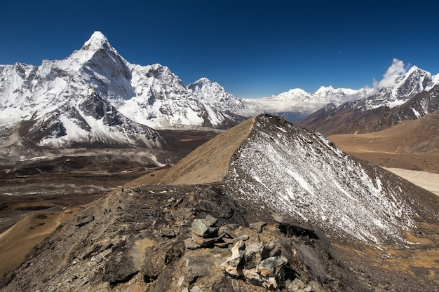 View from the top of a hill with a snowcovered slope of snowcapped mt ama dablam panorama in the himalayas with bright blue sky above and a glacier beneath