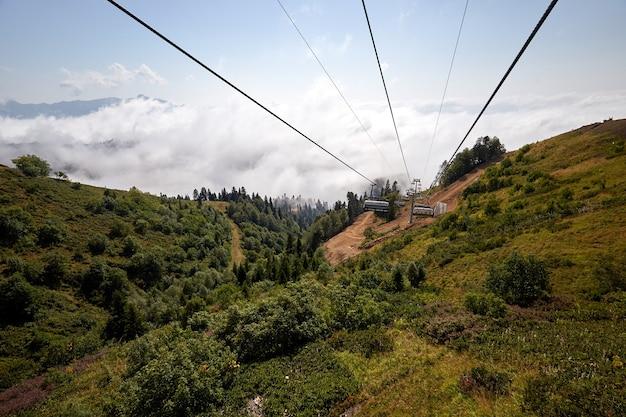 Вид сверху на канатную дорогу с несколькими сиденьями и натянутыми тросами над деревьями в глубоком тумане. горы северного кавказа.
