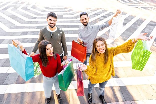 Вид сверху на две пары на открытом воздухе в городе, показывающих свои цветные сумки для покупок, улыбаясь и глядя в камеру
